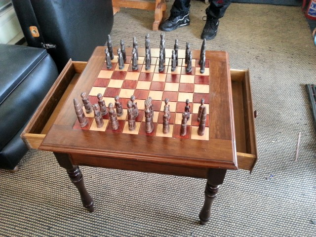 Solid wood chess table with carved wooden pieces. R2500